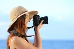 Happy woman on vacation photographing with a dslr camera on the beach with the horizon in the background
