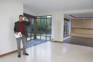 Full length of a male real estate agent photographing new property