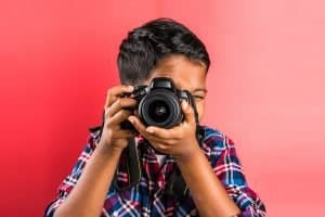 10 year old boy holding digital camera or DSLR camera, posing like a professional photographer, young photographer, kid photographer, child photographer, portrait, closeup, red background